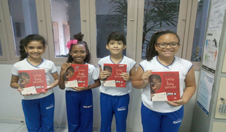 Quatro crianças posam para foto e seguram um livro com as mãos