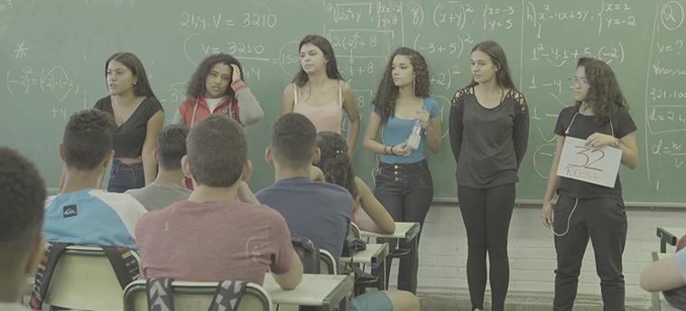 Seis alunas falam com estudantes fazem apresentação para classe