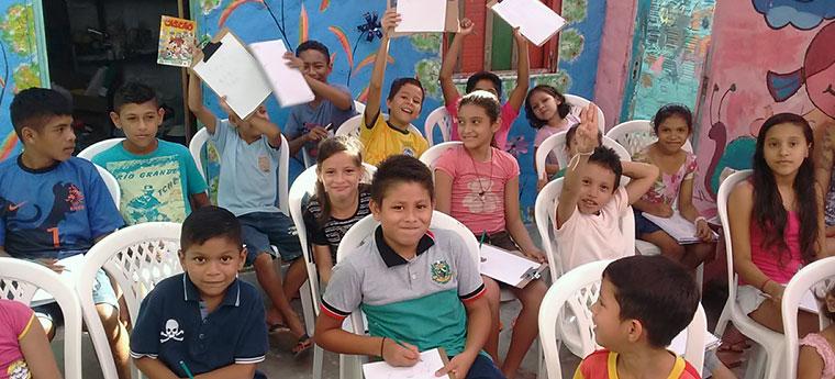 Crianças do projeto Casa do Rio sorriem para foto