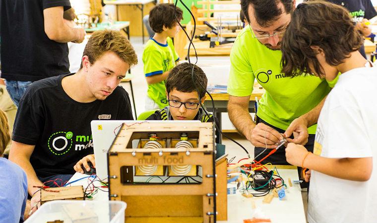 Menino é ajudado por instrutor durante montagem de dispositivo eletrônico em curso da MundoMaker