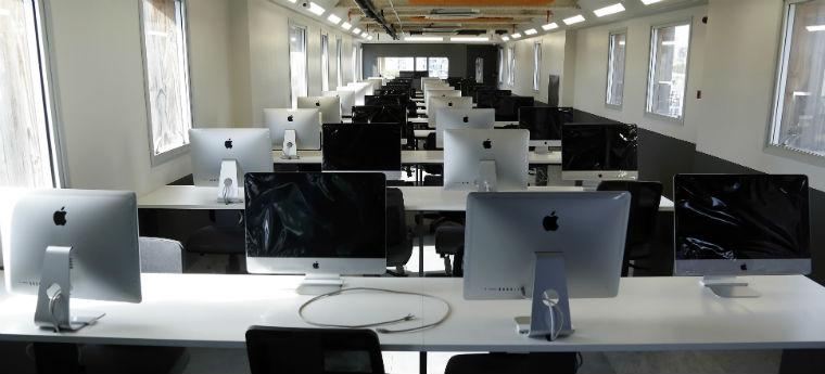 Fila de computadores Apple iMac na Escola 42 de SP