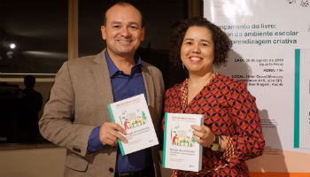 """Foto mostra Alex Gomes e Thaisa Sampaio segurando o livro """"Design de Ambiente Escolar para Aprendizagem Criativa"""""""
