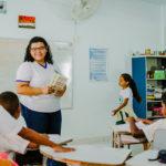 professora segura caderno de elogios e explica atividade para a turma