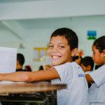 menino segura caderno e sorri para a foto