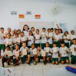 professora posa para foto com toda a sua turma. os alunos seguram o caderno de elogios nas mãos