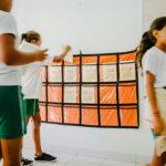menina coloca caderno de elogios em expositor de plástico amarrado na parede