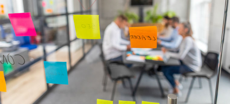 AGITA Edtech - Jovens empreendedores reunidos para uma reunião são vistos em uma sala de vidro com post-its colados nas paredes