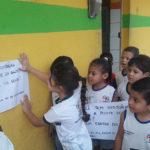 Crianças e a professora colando na parede externa da escola um convite para os moradores da comunidade