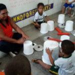 Crianças e estagiária da turma criando sons com os baldes e tampas das panelas
