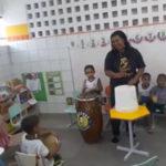 Crianças interagindo com os instrumentos do grupo Muzambê Capoeira Regional