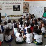Morador da comunidade contando histórias da Ponte do Balde para crianças que estão sentadas no chão da sala de aula
