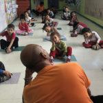 crianças fazem alongamento em aula de yoga