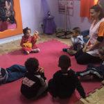 professora senta em círculo com seis crianças