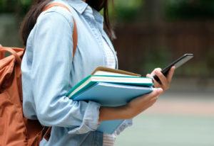 Jovem com mochila nas costas segura livros e celular
