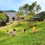 Crianças escalam barranco gramado na escola HN Nursery, no Japão