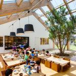 Crianças no refeitório da escola HN Nursery, no Japão. O teto tem abertura para entrada da luz solar