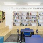 Imagem mostra a biblioteca com mesas azuis e uma pequena arquibancada