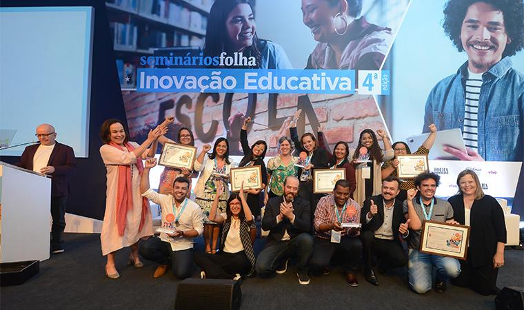 Professores ganhadores do Desafio Inova Escola reunidos no palco exibem o certificado