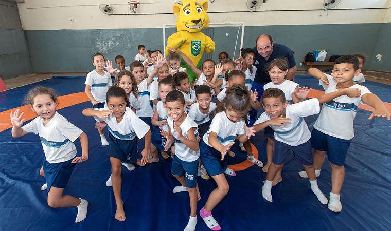 Crianças posam com o mascote Ginga, onça-pintada que representa o esporte olímpico do Brasil