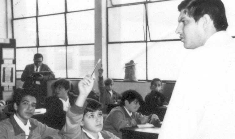 Professor diante de uma sala de alunos. Um deles levanta a mão