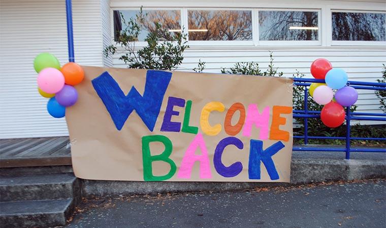 Balões enfeitam a entrada da escola perto de um cartaz welcome back