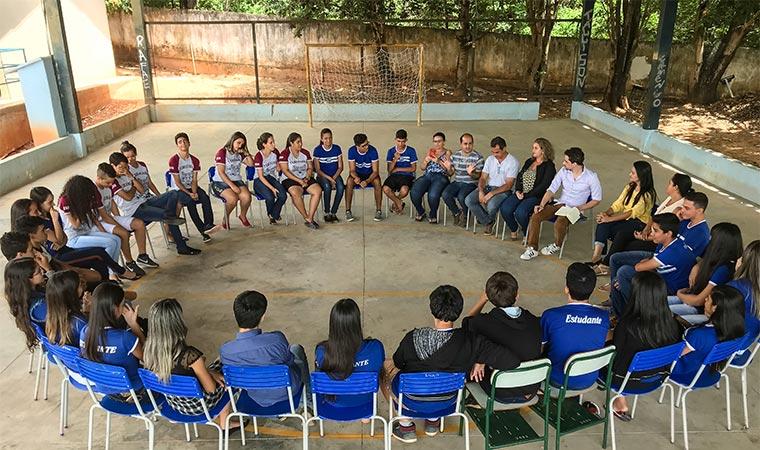 Alunos do Colégio Estadual José Ribeiro Magalhães, em Uruama (GO), participam de roda de conversa na quadra da escola