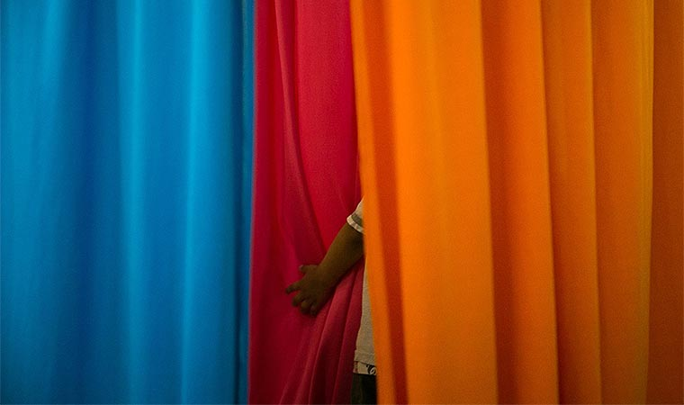 Criança se esconde atrás de tecidos coloridos