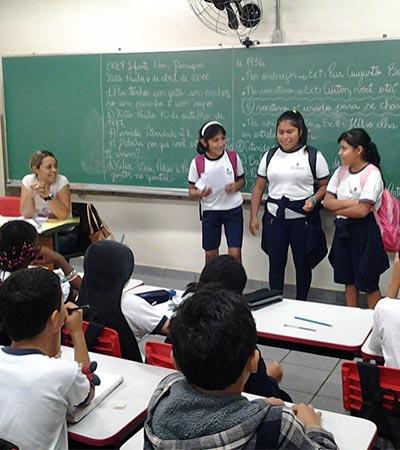Três estudantes do projeto Sí, yo te entiendo! falam diante da classe