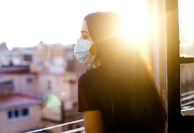 Adolescente em quarentena usando máscara protetora olhando para fora da janela ao pôr do sol