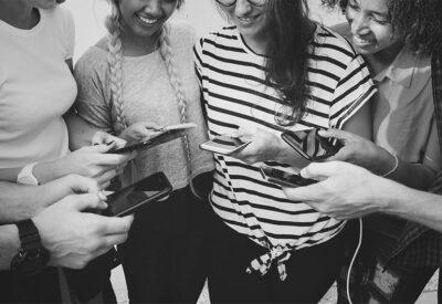 Jovens reunidos mexendo em celular