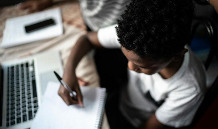 Mãe ajudando filho a estudar com laptop em uma aula online em casa