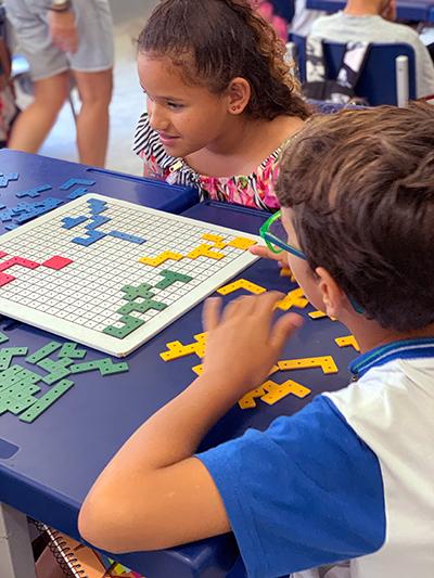 Duas crianças jogam jogo de tabuleiro em uma mesa