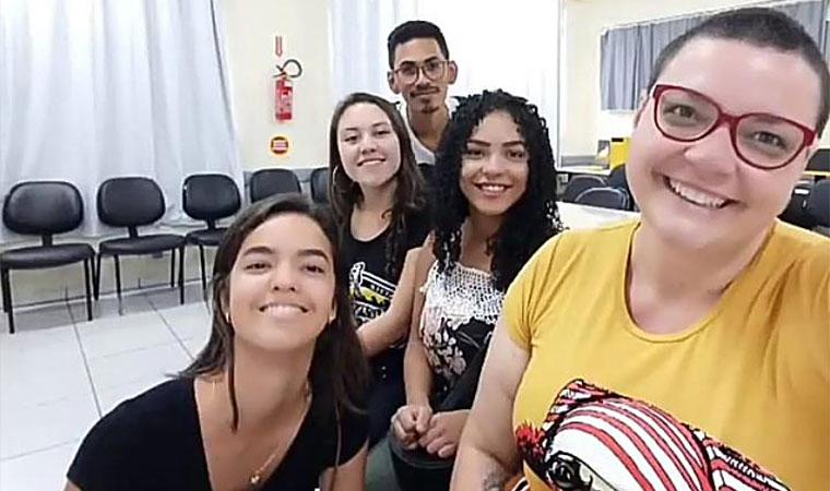 Professora Renata Benedet posa para foto com quatro alunos