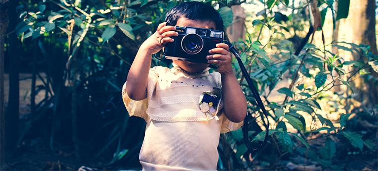 Criança pequena tira foto em meio a floresta