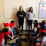 Alunos sentados com olhos vendados enquanto duas colegas comandam atividade de projetos de vida