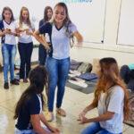 Três alunas durante dramatização em atividade de projetos de vida. Uma em pé gesticula enquanto as outras estão ajoelhadas. Outros colegas assistem ao fundo