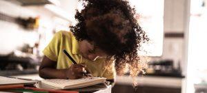 Criança faz trabalho escolar na cozinha de casa