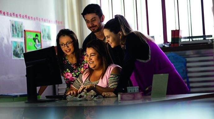 Quatro professores olham tela de computador em uma sala de aula