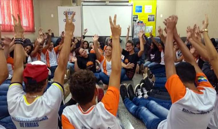 Em uma sala cheia, alunos levantam as mãos durante atividade de mediação de conflitos