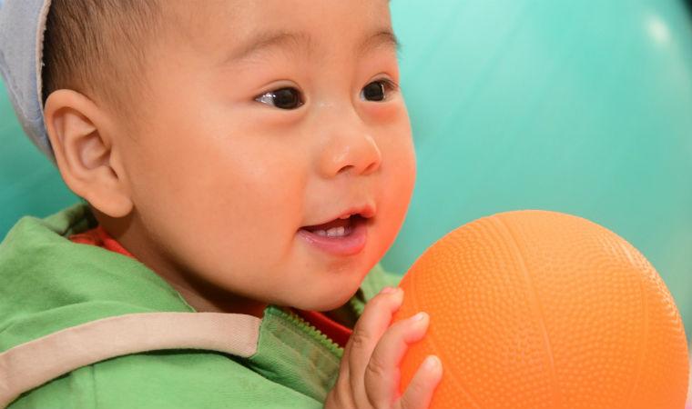 Criança chinesa segurando bola