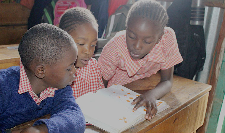 Três crianças leem livros em uma sala de aula