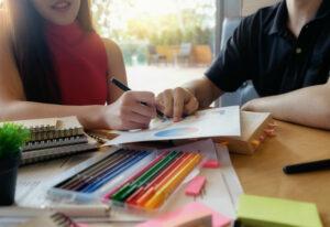 Jovens discutem projeto em uma mesa com relatórios e lápis coloridos
