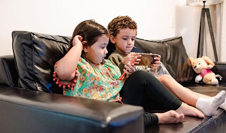 Crianças brincam com celular sentadas no sofá
