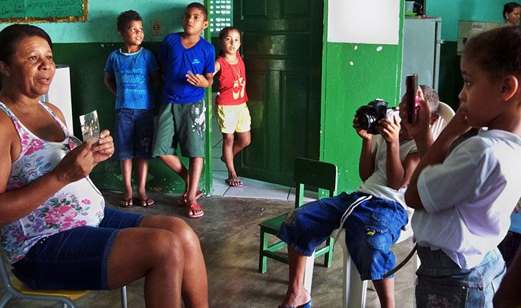 Crianças entrevistam mulher que segura uma foto. Uma criança segura uma câmera e outras assistem ao fundo