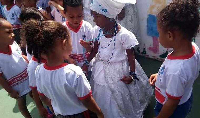 Crianças interagem com outra criança usando roupa afro
