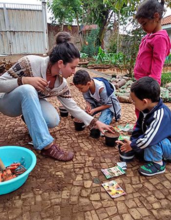 Crianças mexem na horta da escola acompanhadas de uma professora
