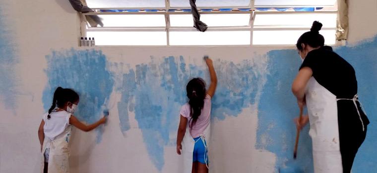Crianças pintando parede da escola