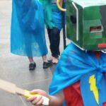 Menino com capa de super-heroi e uma armadura quadrada na cabeça