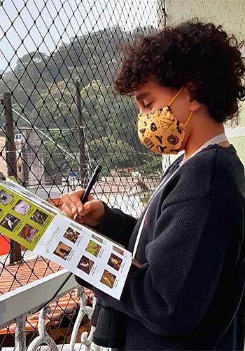 Estudante Henry Oliveira mostra foto em celular com pássaro avistado