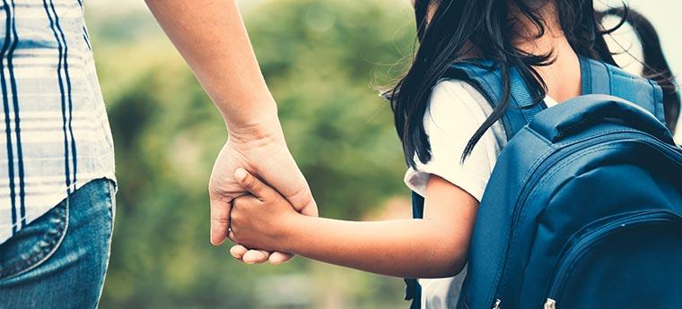Menina com mochila segurando a mão da mãe dela e indo para a escola